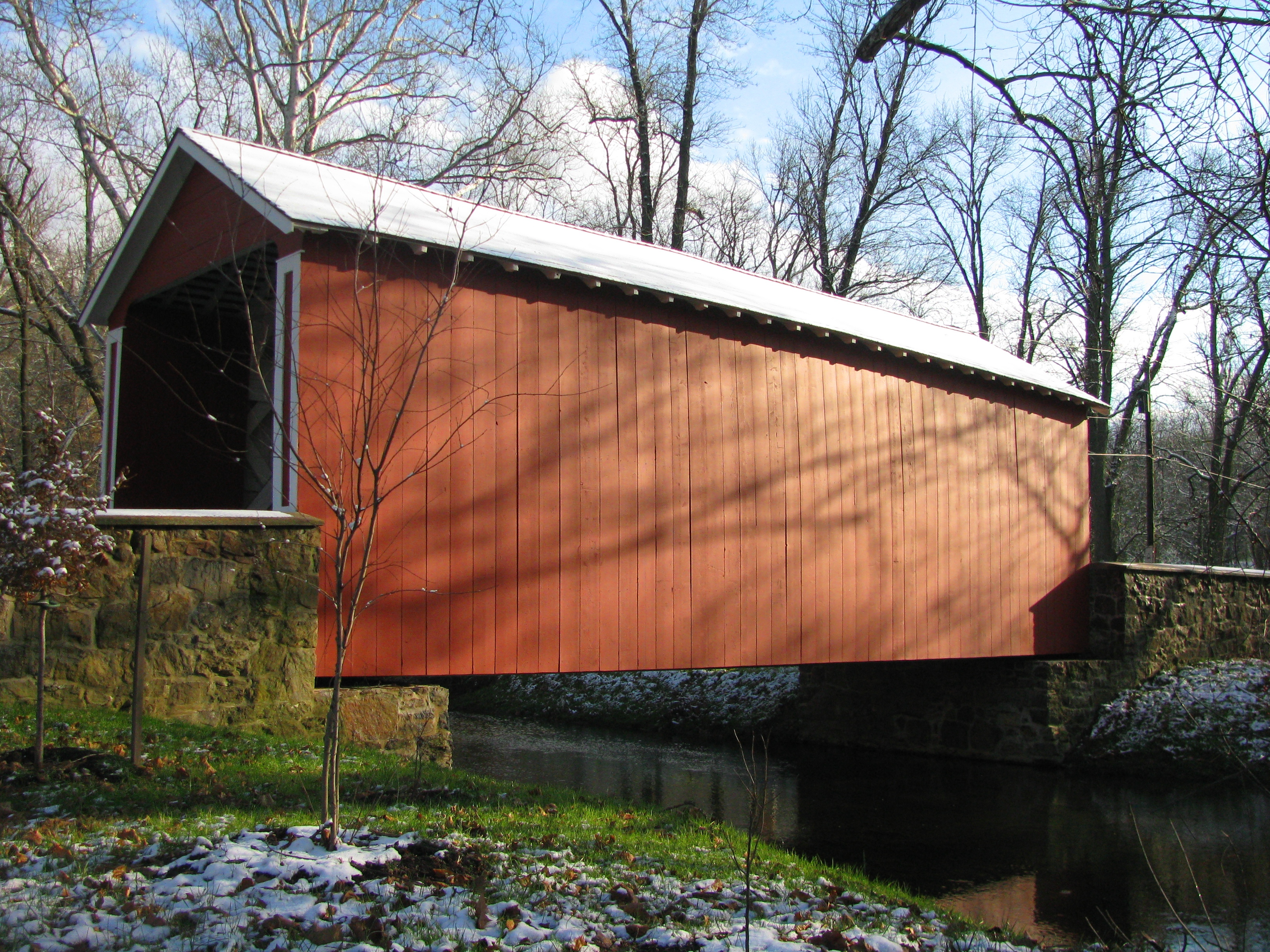 A red bridge with a white snow roof against a blue sky.