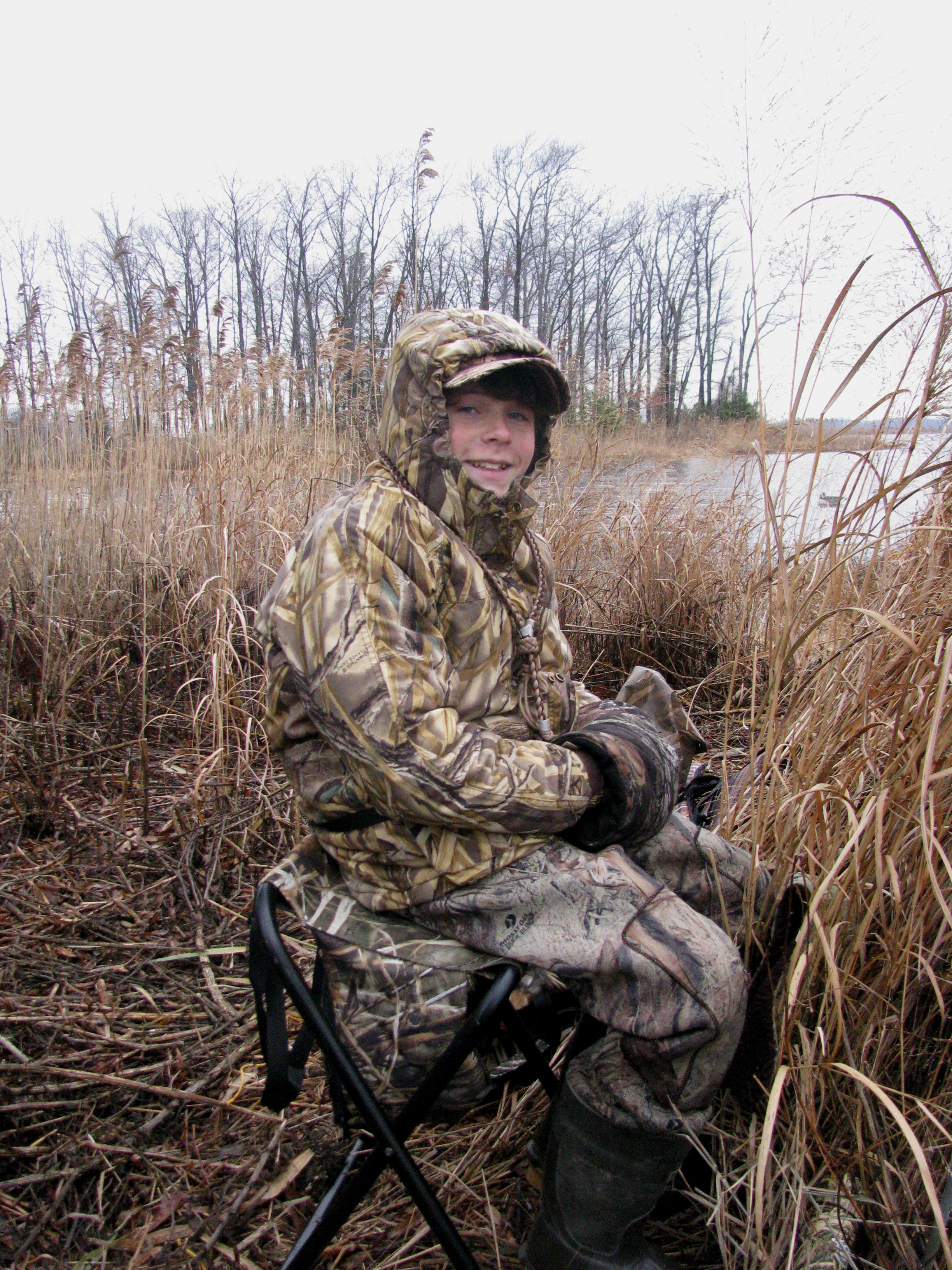Hiding behind the blind in full camouflage, enjoying a morning of waterfowling