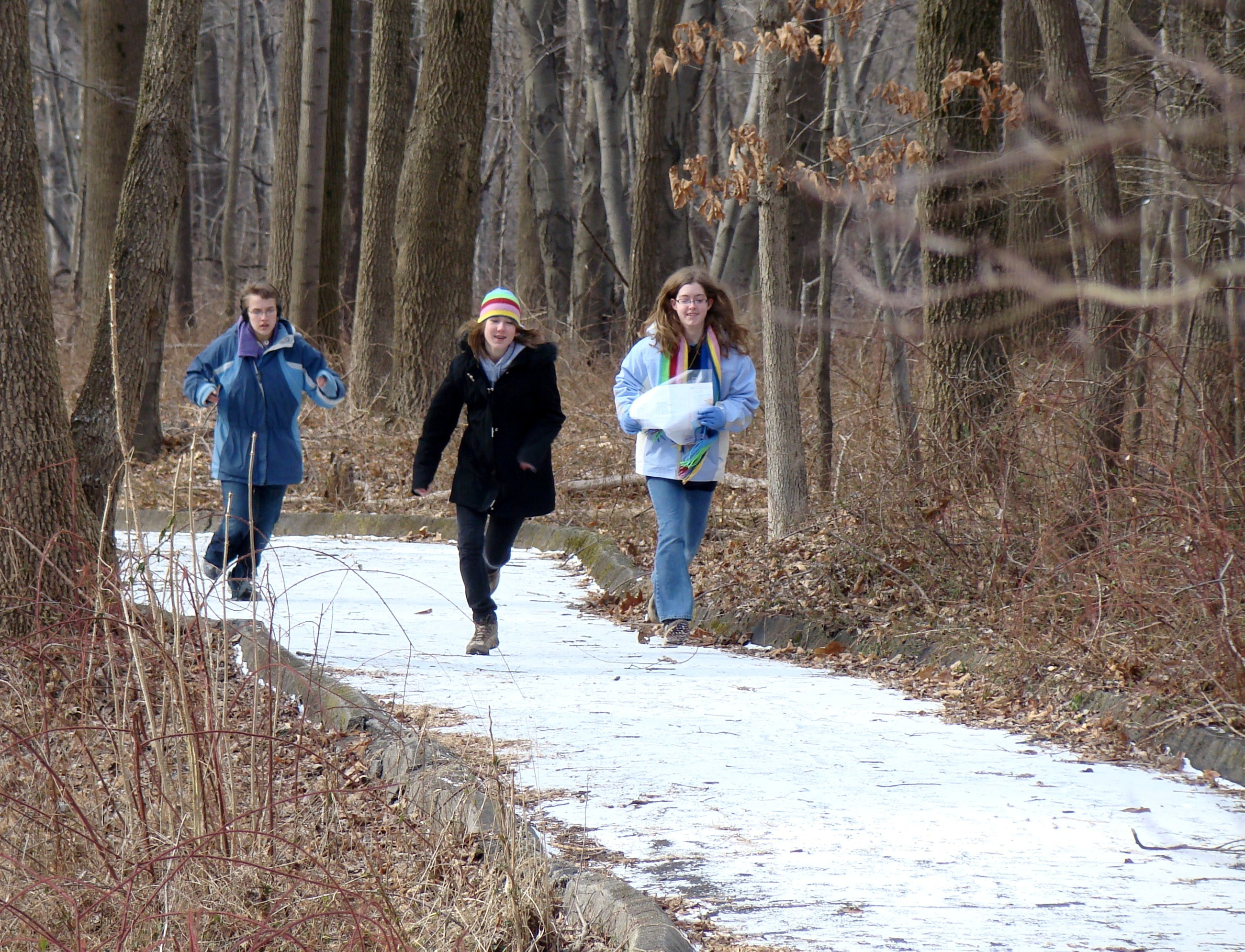 Three Teen Naturalists quickly approaching a waypoint while orienteering at the Schuylkill Center in Philadelphia.