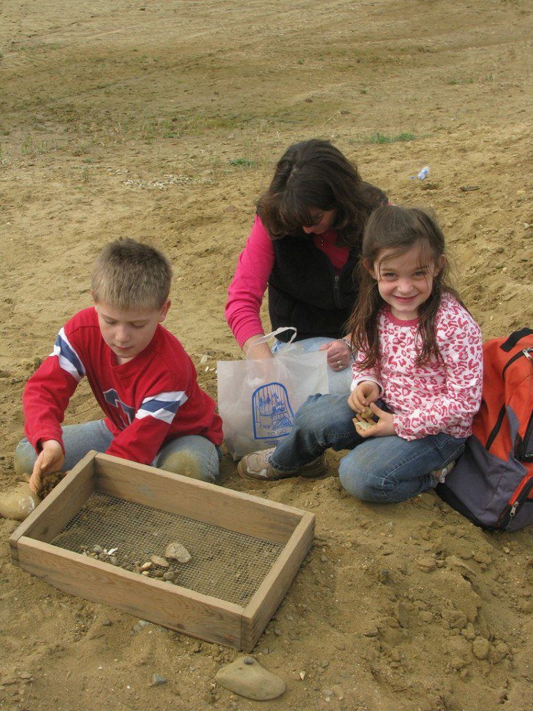 A happy family using a sifting box to sift the sand for fossils at the C&D Canal.