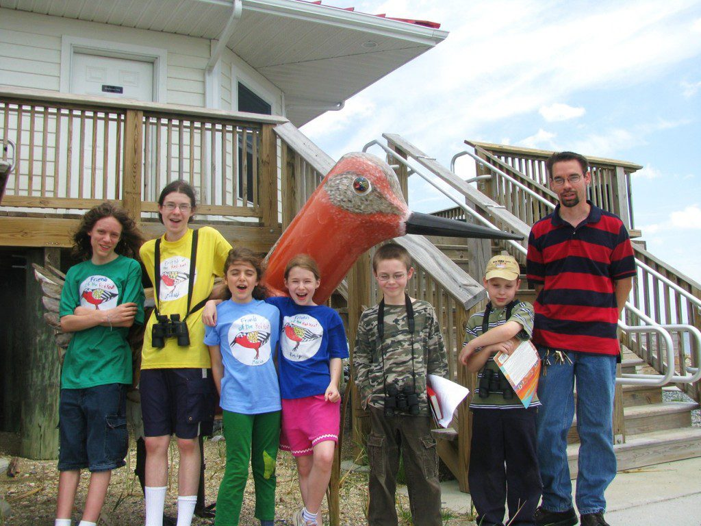 The Friends of Red Knot group surrounds the giant Red Knot sculpture at the DuPont Nature Center.